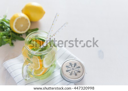 Healthy Spa Water with Fruit. Vitamin water with lemon, mint, celery and cucumber in a jar with straw against a white wood background. Available space at right side. - stock photo