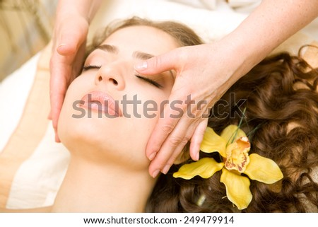 Healthy spa: young beautiful relaxing woman having a facial massage, with orchid in long brown hair - stock photo