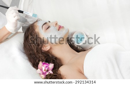 Healthy Spa: Young Beautiful Relaxing Woman Having Moistening Mask Applied. - stock photo