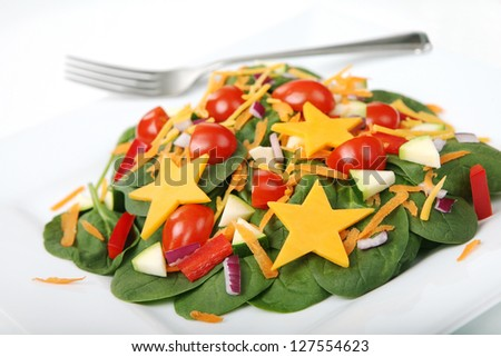 Healthy Spinach Salad with Kid-Friendly Cheese Stars on a White Plate (with focus on front edge of salad)