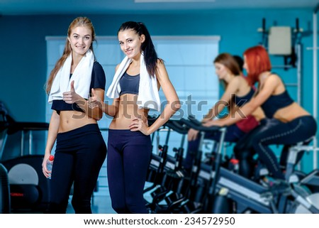 Healthy sport. Two friends are athletes in the gym and look into the camera showing a thumbs up while their friends involved in sports and pedaling on a stationary bike - stock photo