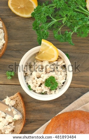 Healthy spread from fish, lemon and parsley with bread on brown wooden background, overhead vertical view