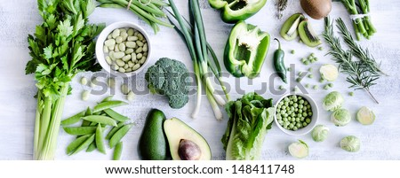 Healthy spread of green vegetables on rustic white background from overhead, broccoli, celery, avocado, brussels sprouts, kiwi, pepper, peas, beans, lettuce, - stock photo