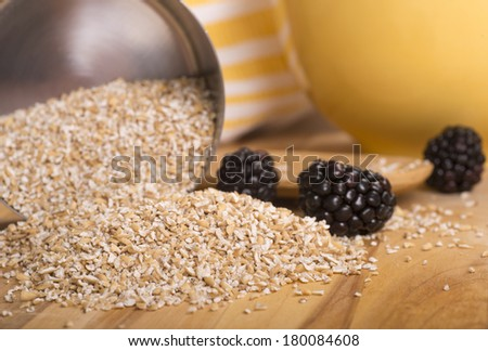 Healthy steelcut whole oats spilling out of a measuring cup with blackberries - stock photo