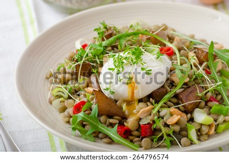 Healthy summer lentil salad with caramelized pear, arugula and poached egg soft on top - stock photo