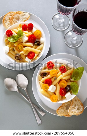 Healthy summer light pasta salad with fresh raw tomatoes, anchovies and capers. glasses of red wine - stock photo