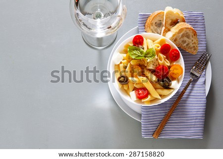 Healthy summer light pasta salad with fresh raw tomatoes, anchovies and capers. glasses with water. background for restaurants - stock photo