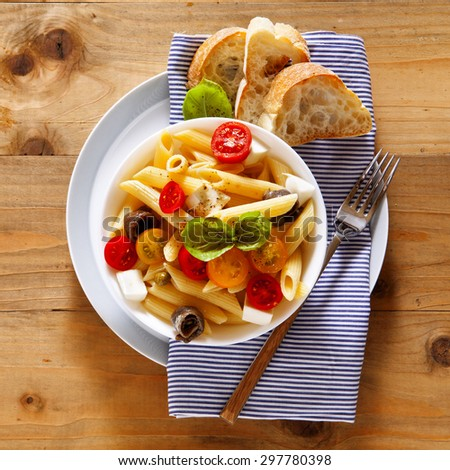 Healthy summer light pasta salad with fresh raw tomatoes, anchovies and capers. on wood - stock photo