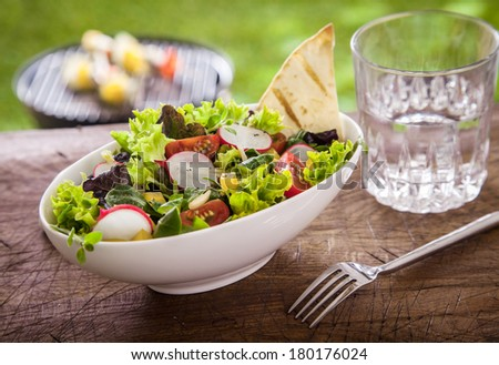 Healthy summer salad with lettuce, bell pepper, tomato and radish served with a glass of fresh water on a rustic wooden garden table - stock photo