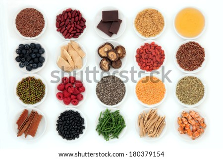 Healthy super food selection in porcelain bowls over white background. - stock photo