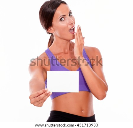 Healthy surprised brunette woman with a hand to her mouth holding copy space while looking at camera wearing violet and black gymnastic clothing, isolated - stock photo