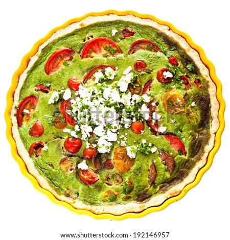 Healthy tasty vegetarian quiche in a decorative fluted pie plate isolated on white with a clipping path, overhead view