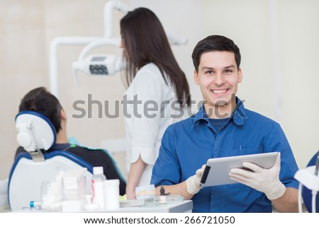 Healthy teeth and dental healthcare. Portrait of professional dentist doctor. His colleague stomatologist is working with patient on the background. - stock photo