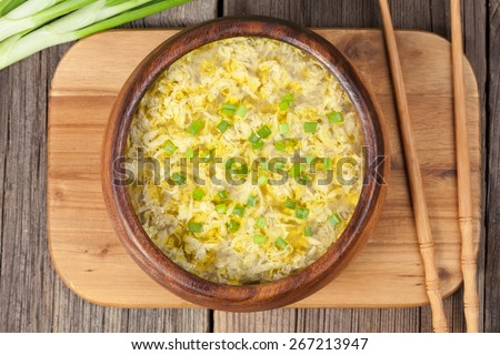 Healthy traditional asian food drop egg soup with broth on wooden desk on vintage background