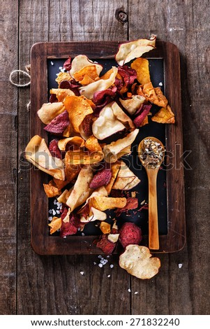 Healthy vegetable beetroot, sweet potato and white sweet potato chips on a black board with spoon of seasoning over rustic background. Top view - stock photo
