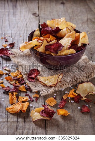 Healthy vegetable beetroot, sweet potato and white sweet potato chips on over rustic background - stock photo