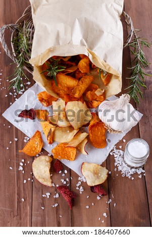 Healthy vegetable beetroot, sweet potato and white sweet potato chips on  paper with sea salt, rosemary and garlic on a rustic wooden background closeup - stock photo