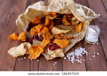 Healthy vegetable beetroot, sweet potato and white sweet potato chips on paper with sea salt on a rustic wooden background - stock photo