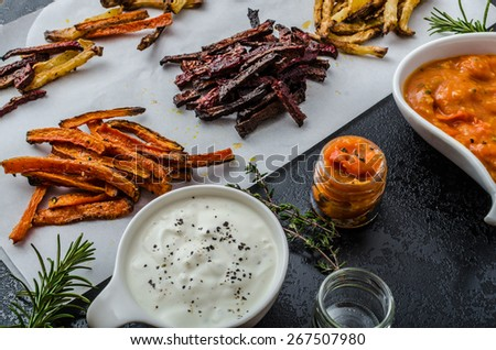 Healthy vegetable chips - beet, celery and carrots, tomato and garlic dip with herbs, fresh herbs inside - stock photo