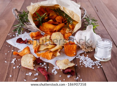 Healthy vegetable chips on  paper with sea salt, rosemary and garlic on a wooden background closeup - stock photo