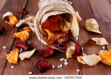 Healthy vegetable chips with sea salt in a vintage paper wrap on a rustic wooden background - stock photo