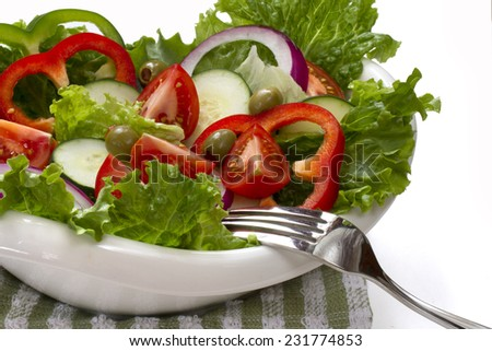 Healthy vegetable salad in a white bowl. Isolated on white.