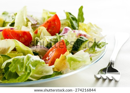 Healthy vegetable salad served on a white plate with silver fork  - stock photo