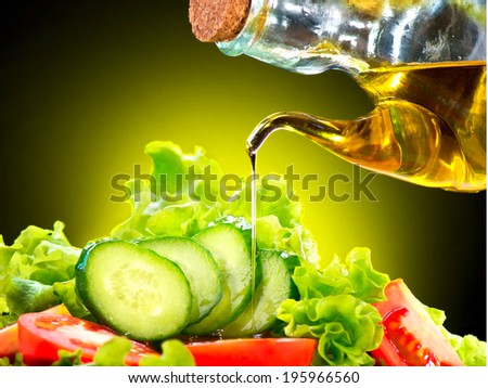 Healthy Vegetable Salad with Olive oil dressing. Pouring Olive oil. Healthy vegetarian food. Vegan. Diet, dieting concept. Lettuce, tomatoes, cucumbers. Organic bio food. - stock photo