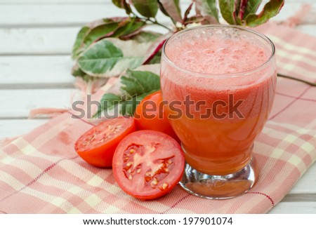 Healthy vegetable smoothie made of red ripe tomatoes smoothies on white table. - stock photo