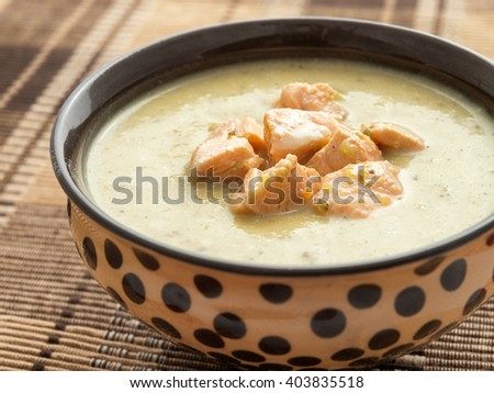Healthy vegetables cream soup with chicken blocks and cream, shot from above, horizontal shot