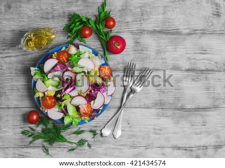 Healthy vegetarian food, fresh vegetables salad with different vegetables radishes, cherry tomatoes, lettuce salad, olive oil, fresh whole radishes,  blue plate, light wooden background, top view - stock photo