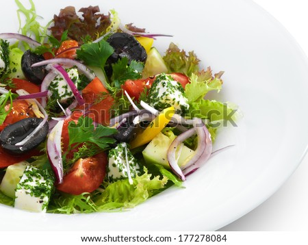 Healthy vegetarian greek salad with tomatoes, feta cheese and olives served on a white round plate. Isolated on white - stock photo