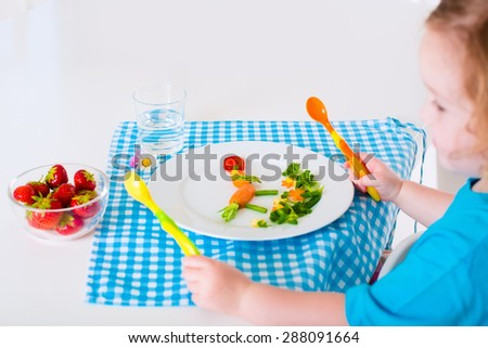 Healthy vegetarian lunch for little kids. Kid meal. Vegetable and fruit served as animals, corn, broccoli, carrot, strawberry helping child to learn eating right and clean, children hands with spoon - stock photo