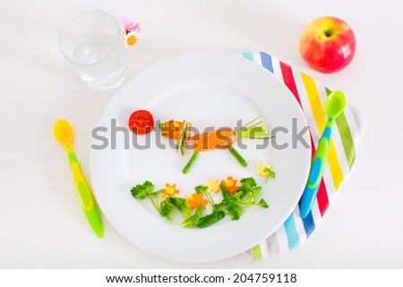Healthy vegetarian lunch for little kids, vegetables and fruit served as animals, corn, broccoli, carrots and fresh strawberry helping children to learn eating right and clean - stock photo