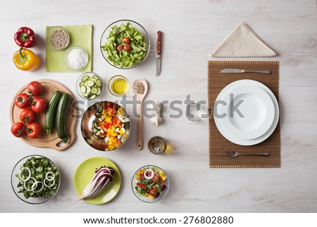 Healthy vegetarian meal concept with table set and fresh raw vegetables - stock photo