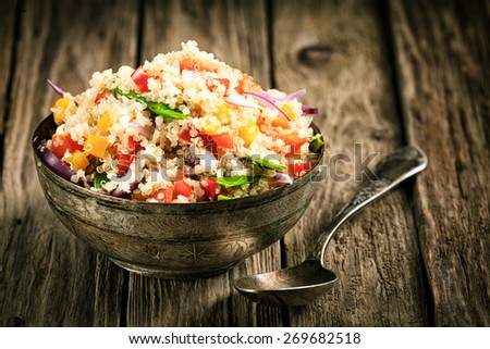 Healthy vegetarian quinoa recipe with colourful bell pepper, tomato, onion and fresh herbs in a rustic metal bowl on an old wooden kitchen counter - stock photo