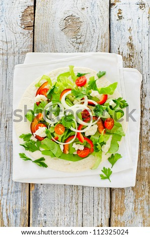 Healthy vegetarian salad with tomato onion cheese in pita sandwich - stock photo
