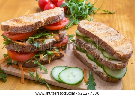 Healthy Vegetarian Sandwiches on a Chopping Board with Ingredients in the Background