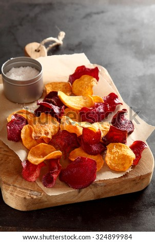 Healthy vegetarian snack of crisp crunchy fried or oven-baked beetroot chips served with rock or sea salt on a wooden chopping board , close up high angle view with copyspace behind - stock photo