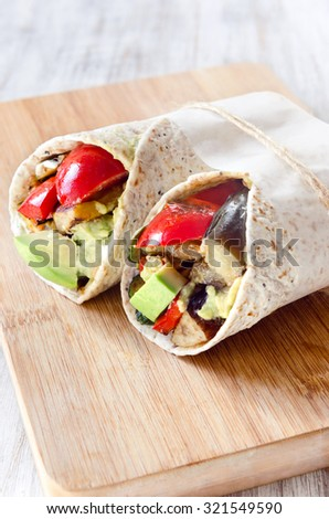 Healthy vegetarian vegan tortilla wraps with roasted vegetables like aubergine eggplant, red bell peppers, avocado  - stock photo