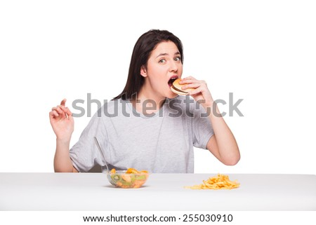 healthy versus junk food concept with a natural woman heaving in front fruits meal and choosing fries with hamburger, isolated on white - stock photo