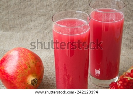 Healthy vitamin beverage: fresh made pomegranate juice. Pomegranate in the background - stock photo