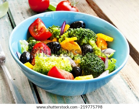 Healthy Warm Salad with Broccoli,Tomatoes, Red Onion and Olives in a Blue Bowl - stock photo