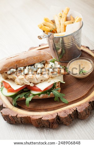 Healthy wheat sandwich burger with BBQ  grilled chicken steak, cheese, tomato, rocket salad, cucumber, fried potato and mustard sauce  served for eating on wooden board