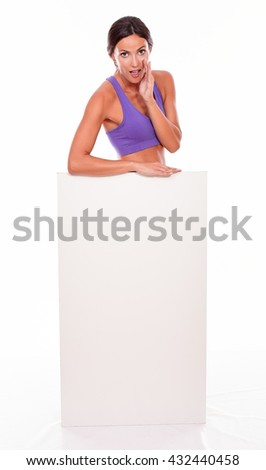 Healthy whispering brunette woman standing behind a blank placard and looking at camera, one hand to her cheek while wearing violet gymnastic clothing isolated - stock photo