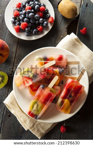 Healthy Whole Fruit Popsicles with Berries Kiwi and Peaches - stock photo