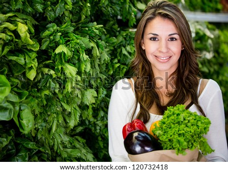 Healthy woman buying fresh vegetables at the supermarket - stock photo