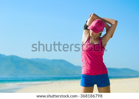 Healthy woman doing exercising on the beach. Freedom, vacation, fitness and health care concept with copy space over natural background