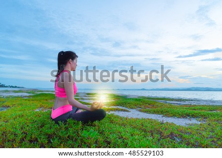 Healthy woman doing yoga exercises on the beach with sunset morning at Phuket, Thailand