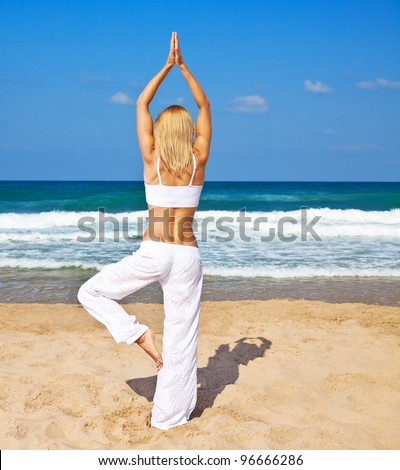 Healthy woman doing yoga posture, female exercising on the beach, slim sporty girl training body, lady workout, rear view,  fitness and health care concept - stock photo